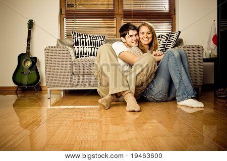 Feliz pareja de jóvenes que se divierten en el sofá