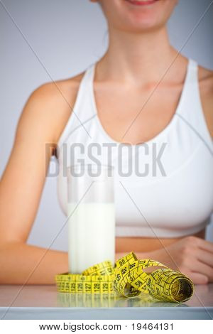 Glass filled with milk surrounded with measuring tape, smiling woman in the background