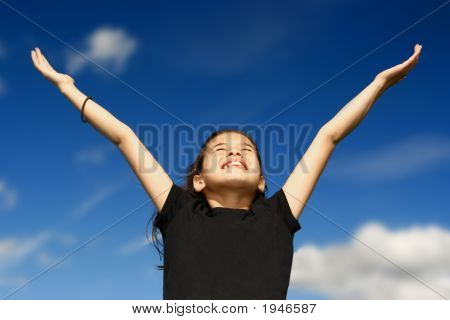 Girl With Arms Wide Open Against Blue Sky