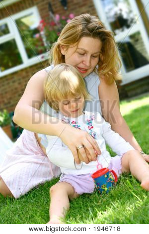 152 Mother Assisting Her Girl Toddler With Bubble Mixture