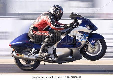 Slow shutter speed shot of a motorcycle accelerating down a race track (motion blur)
