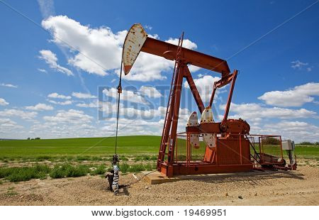 Red Oil field pump jack on the prairie