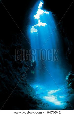 Silhouette of a diver with sun rays in a cave