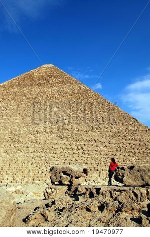 A young women in red in front of great pyramid Keops of Giza, Cairo Egypt