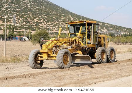 A construction vehicle flattening a road