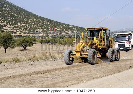 A construction vehicle flattening a road and a truck at the background