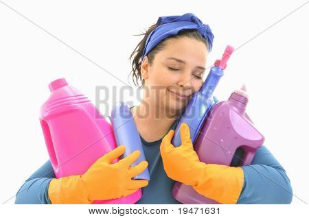 Happily smiling eyes shut maid hugging a bunch of cleaning products with love. White background studio picture.