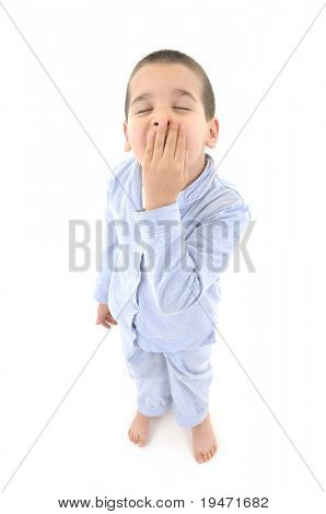 White background studio image  5-6 years old sleepy boy in pajamas.