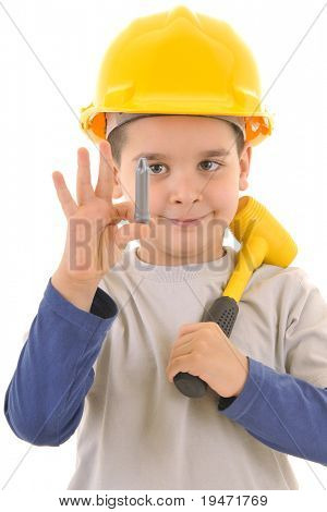 Little kid as a construction worker wearing yellow helmet and yellow hammer on his shoulders. White background vertical  studio picture.