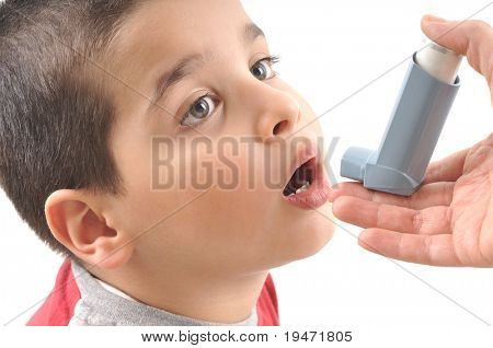 Close up image of a cute little boy opening his mouth to use inhaler for asthma. White background studio picture.