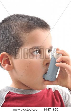 Close up image of a cute little boy using inhaler for asthma. White background vertical studio picture.