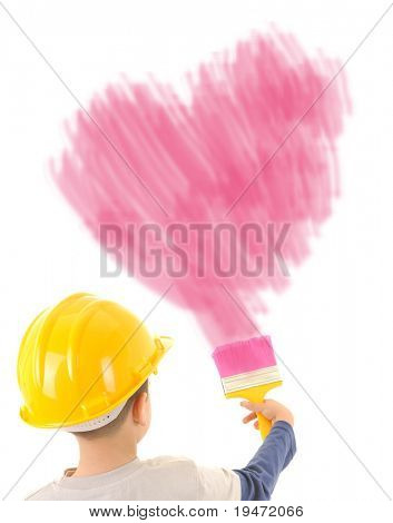 Adorable 6 years old boy wearing yellow helmet painting a big pink heart on the wall. High resolution studio image.