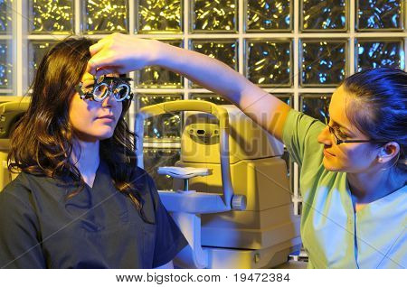 Beautiful young female patient having a medical examination at optician - a series of dramatically lightened eye exam related pictures.