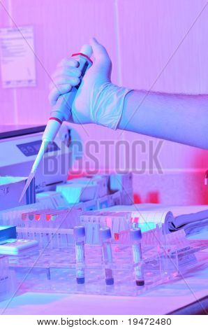 Glass measurer dripping fluid into tubes in a dramatically lightened pathology lab