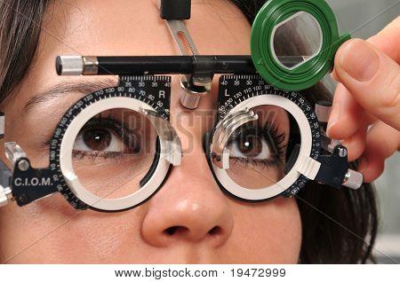 Paciente femenino joven hermoso tener un examen médico en óptica - una serie de ojo examen relat
