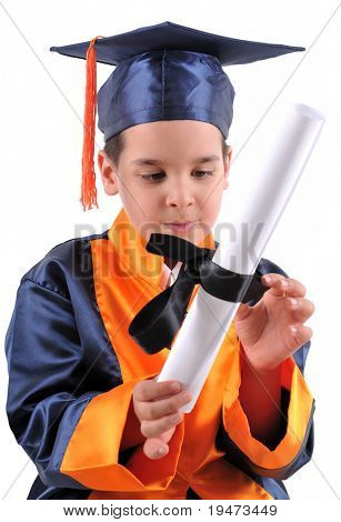 Elementary boy wearing graduation cap and gown proudly holding his diploma.