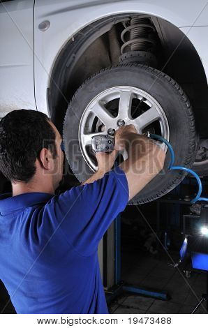 Car mechanic removing wheel nuts to check brakes - a series of MECHANIC related images.