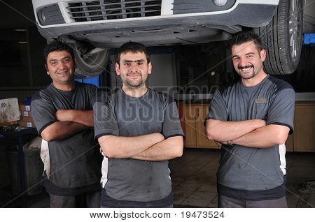 Auto mechanics smiling in car service - a series of MECHANIC related images.