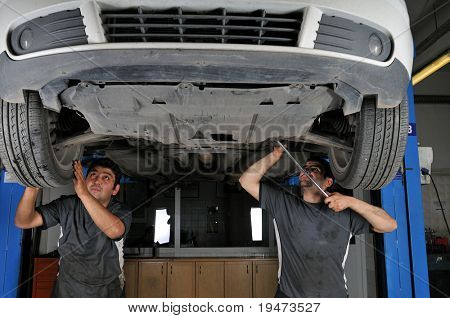 Auto mechanics working under the car - a series of MECHANIC related images.