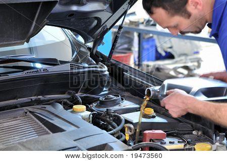 Óleo de mudança mecânico de carro - modelo e movimento borrado de óleo.