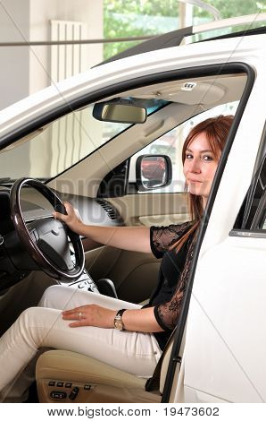 Female driver testing a new car at a showroom of dealer - a series of BUYING A NEW CAR images.