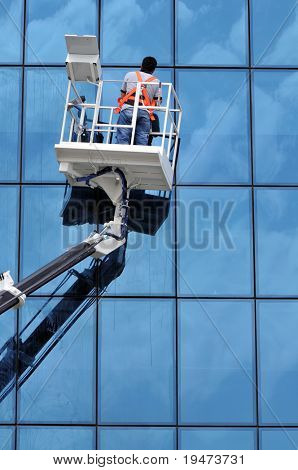 Vertical image of a window cleaner working on a glass facade in a gondola