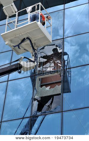 Lift operator changing the broken windows of an office
