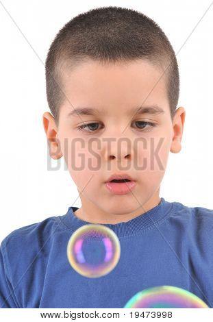 Little boy blowing soap bubbles - white background studio image.