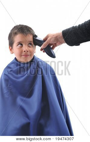 Barber cutting little child's hair with scissor over white background
