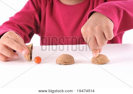 Cute boy playing traditional shell game with three walnut shells - a series of SHELL GAME images.