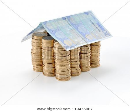 Money house made from lots of coins and euro banknote roof - isolated with reflection