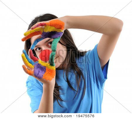 Harlequin teenager with hands painted in colorful paints looking through her hands - SEE MORE RELATED IMAGES.