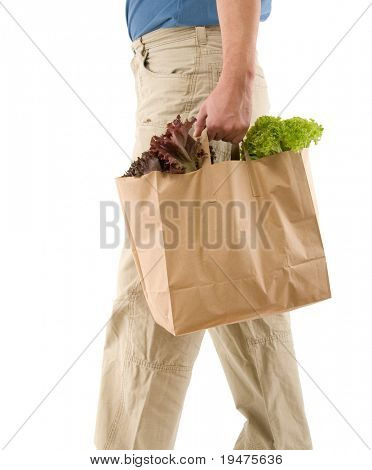 Adult man walking with paper bag full of groceries isolated on white background.