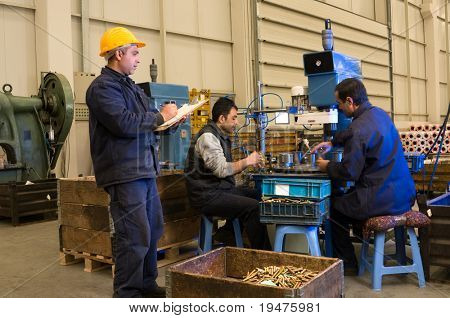 Inspector checking workers at factory motion blurred - a series of INDUSTRIAL images.