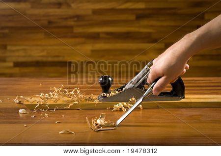 Hand of a carpenter using wood plane.