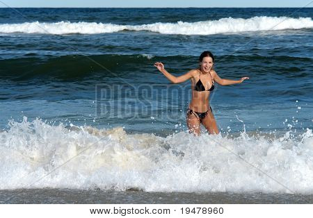 Smiling young woman playing with waves on the beach