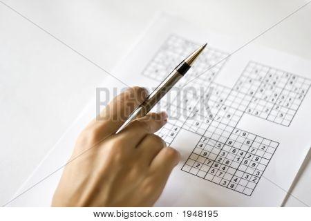 Una mano en la cuadrícula de Sudoku