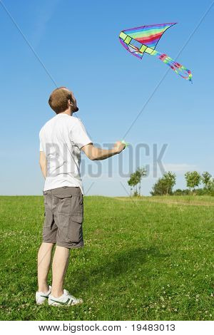 Man In White Shirt Standing On Summer Meadow And Flying Multicolored Kite, Full Body, Blue Sky