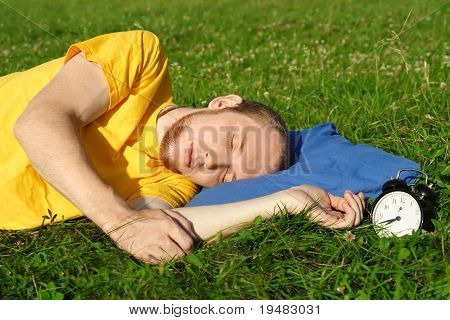 Man In Yellow Shirt Sleeping In Summer Meadow Near Clock, Lying On Side, Rest Concept