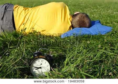Man In Yellow Shirt Sleeping On Summer Lawn Near Alarm Clock, Half Body, Focus On Clock