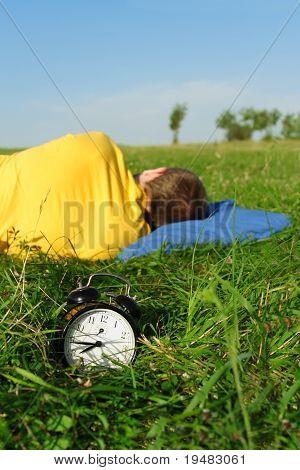 Man In Yellow Shirt Sleeping On Summer Lawn Near Alarm Clock, Half Body