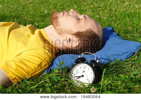 Man White Breard In Yellow Shirt Sleeping On Summer Meadow Near Clock, Lying On Back, Rest Concept