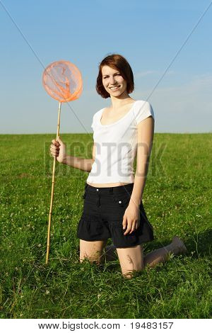 Young Girl In White Shirt Sitting On Knees On Summer Meadow And Holding Butterfly Net