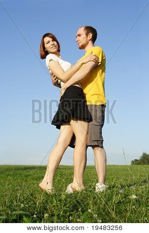 Young Man In Yellow Shirt And Redhead Girl Embracing, Standing On Summer Lawn, Full Body
