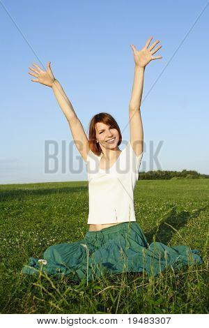 Young Beauty Girl In Long Skirt Sitting On Summer Lawn, Putting Hands Up And Smiling