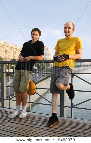Two Young Men In Sport Clothes Standing On Bridge And Smiling, Looking At Camera
