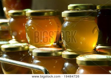 many honey jars on a shelf in a warehouse