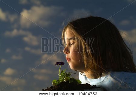 young girl smelling a pansy flower against cloudy sky