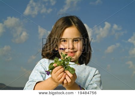 girl with one tooth missing holding plant with flower