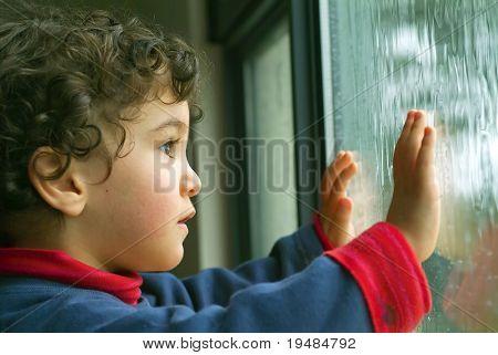 kleiner Junge, den Regen durch das Fenster beobachten